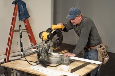 man cutting wood board with professional electric chop saw