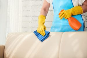man cleaning the sofa with spray and towel