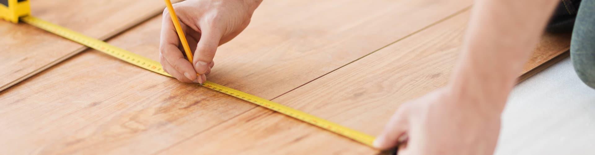 man measuring a floor
